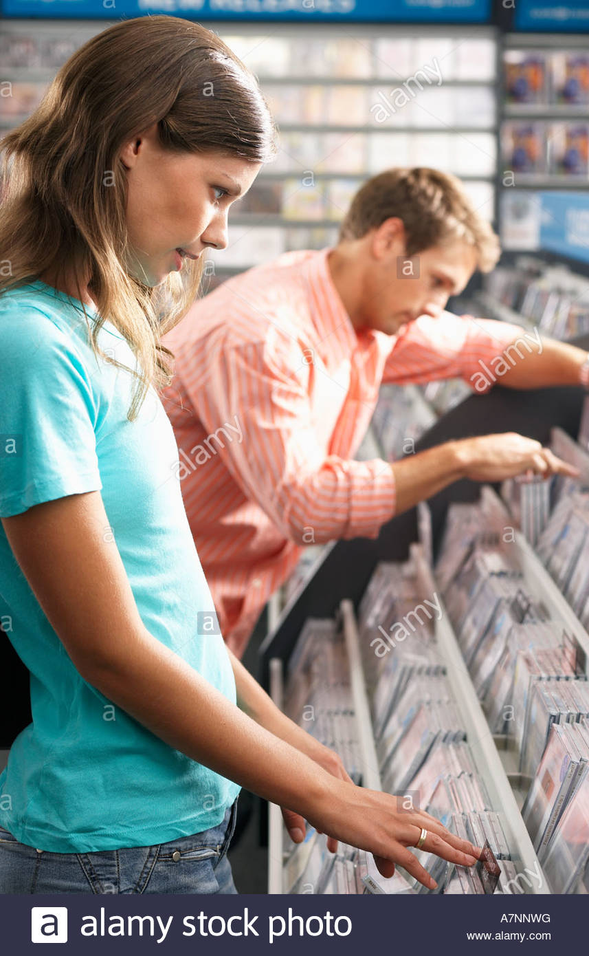 Young couple choosing CD s in record shop side view - Stock Image
