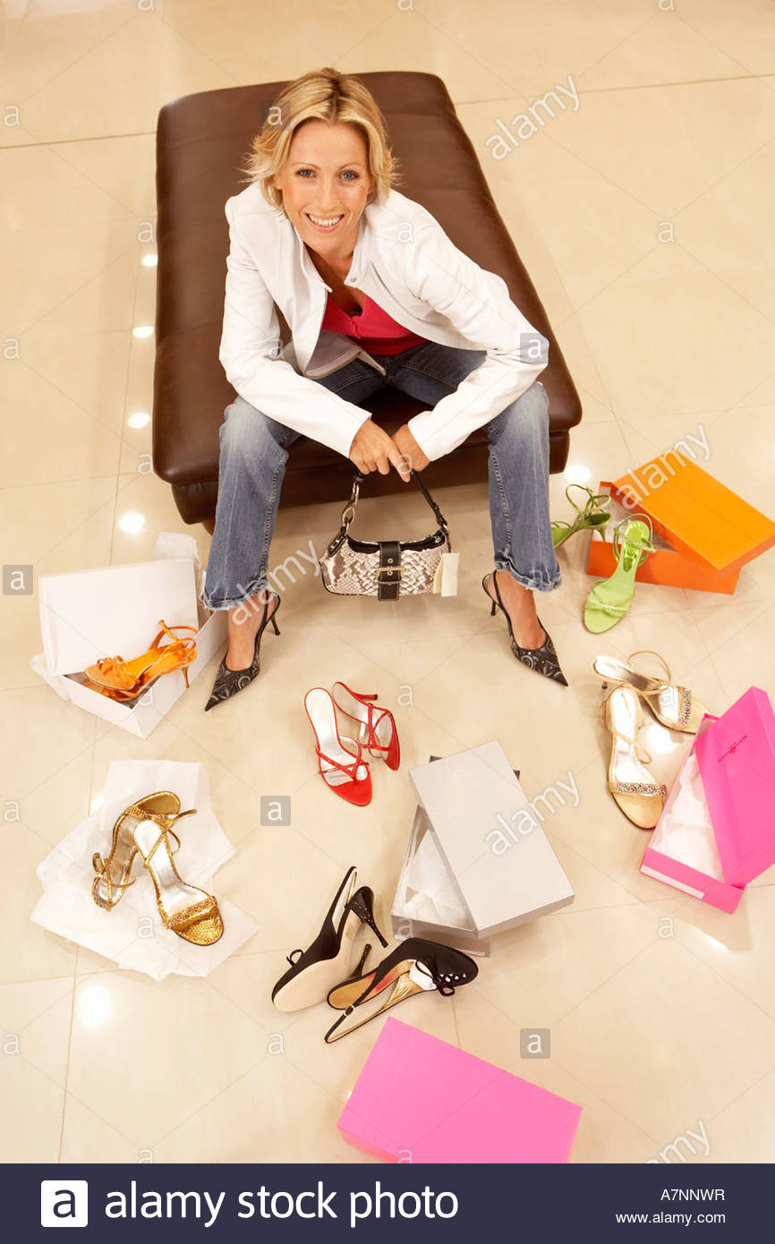 Blonde woman trying on different pairs of high heels in shoe shop portrait elevated view - Stock Image