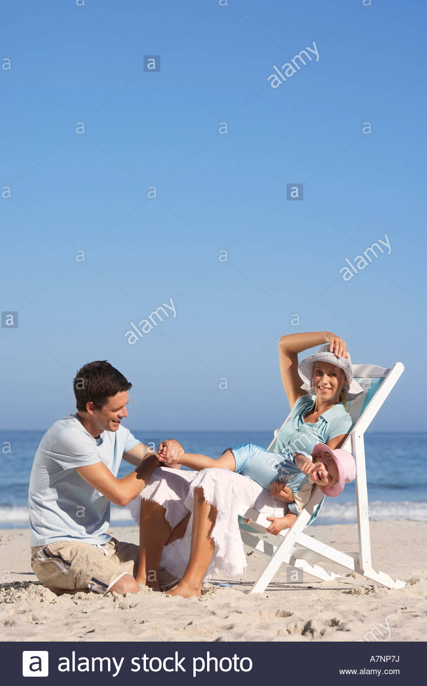 Young family sitting on sandy beach daughter 2 3 lying in mother s lap portrait Stock Photo