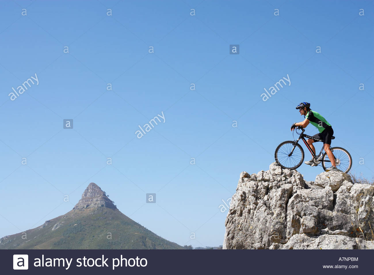 South Africa male mountain biker standing at edge of rock looking at view profile - Stock Image