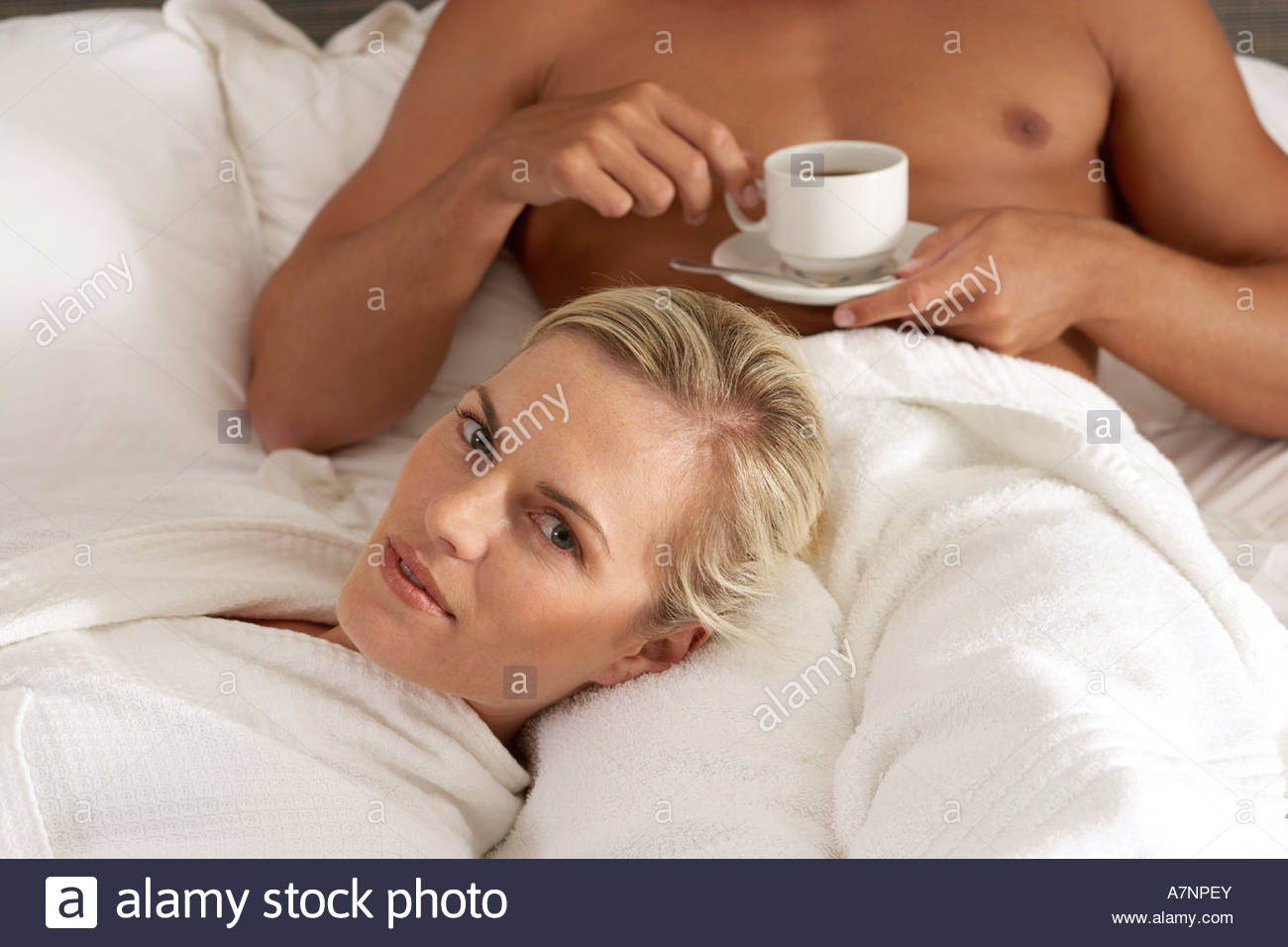 Couple relaxing on bed man drinking cup of coffee woman resting head in man s lap portrait - Stock Image