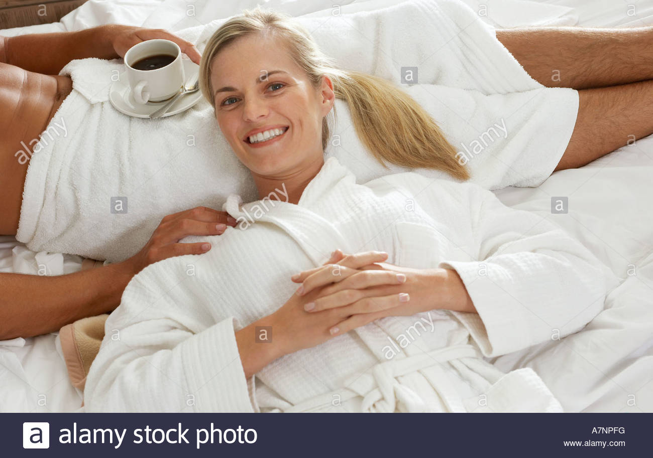 Couple relaxing on bed with coffee woman s head in man s lap smiling elevated view portrait - Stock Image
