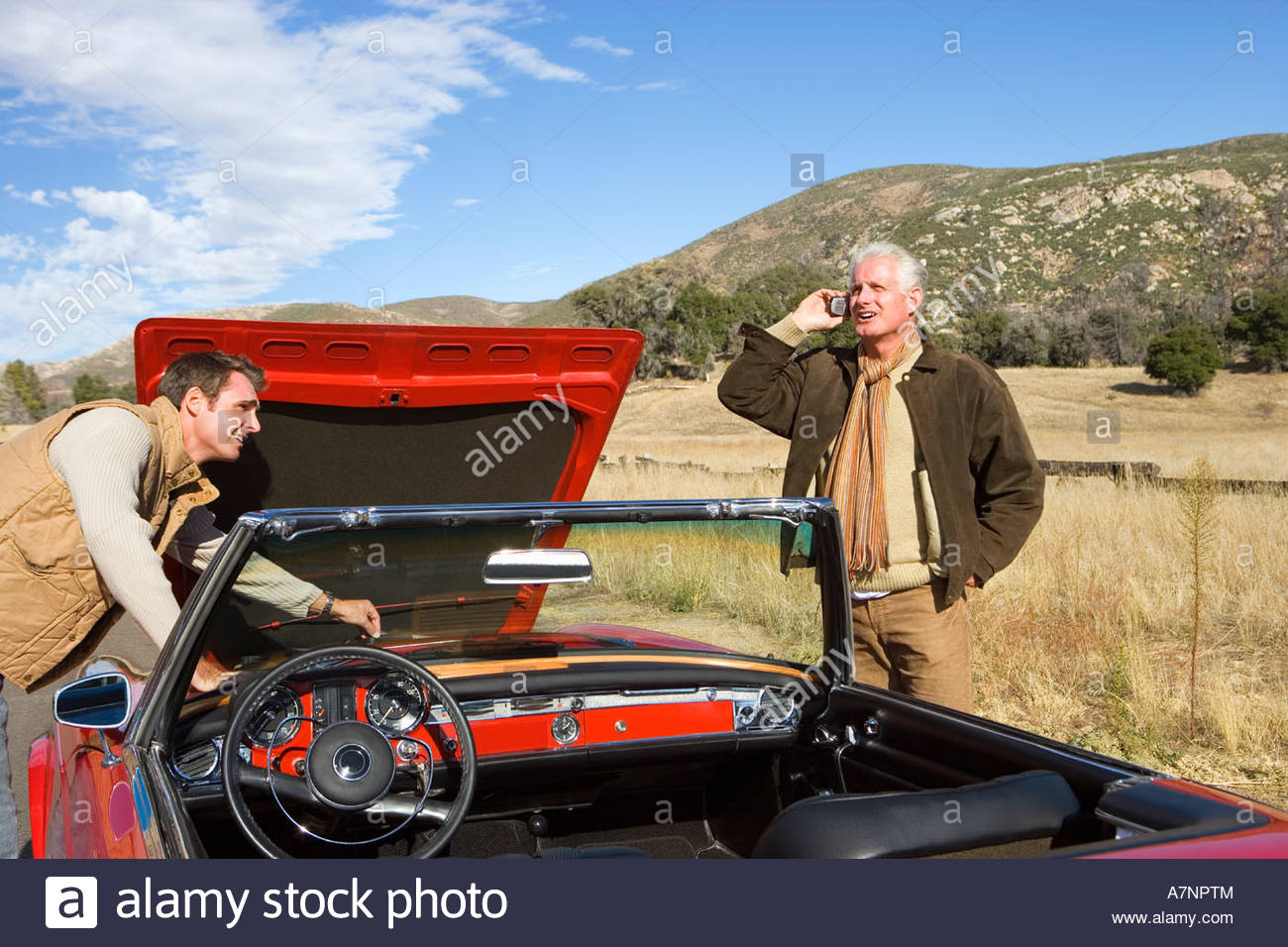 Father and son experiencing car trouble on country road man looking at engine senior man using mobile phone - Stock Image