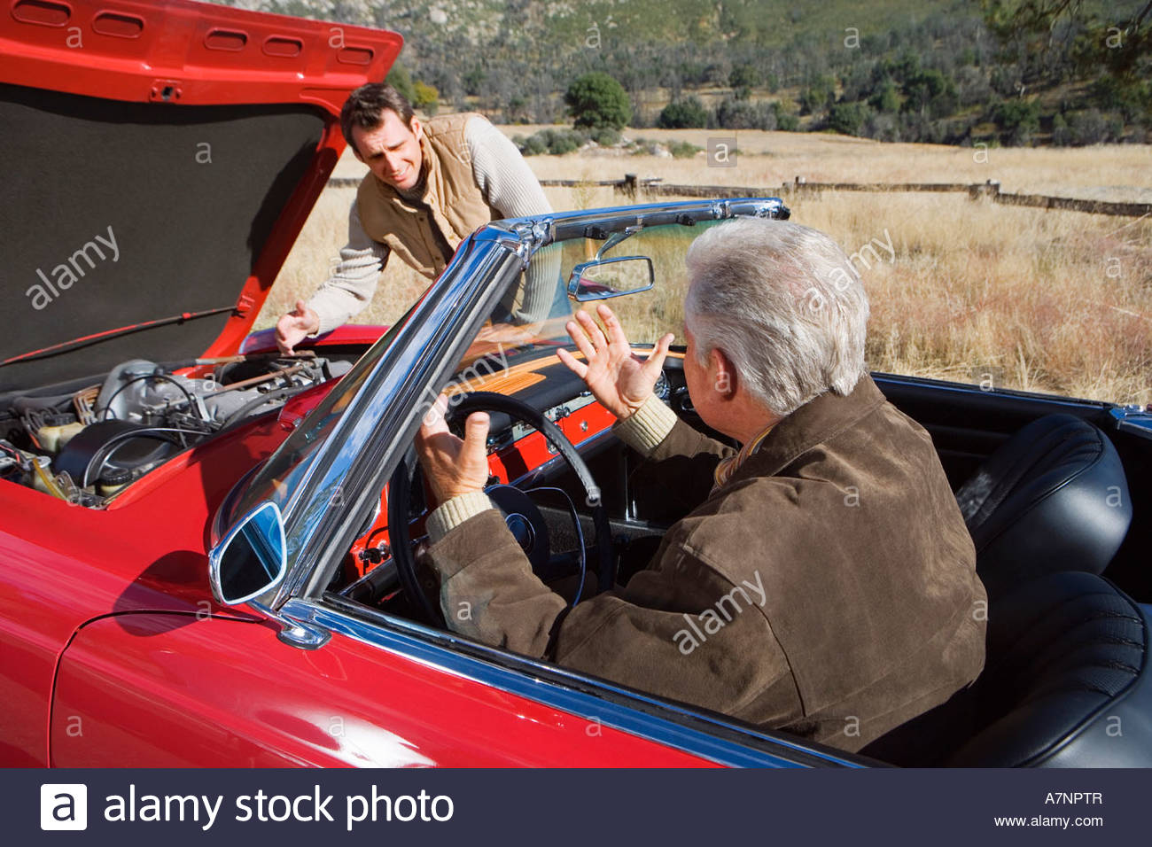 Father and son experiencing car trouble on country road man looking at engine senior man sitting in driver s seat - Stock Image