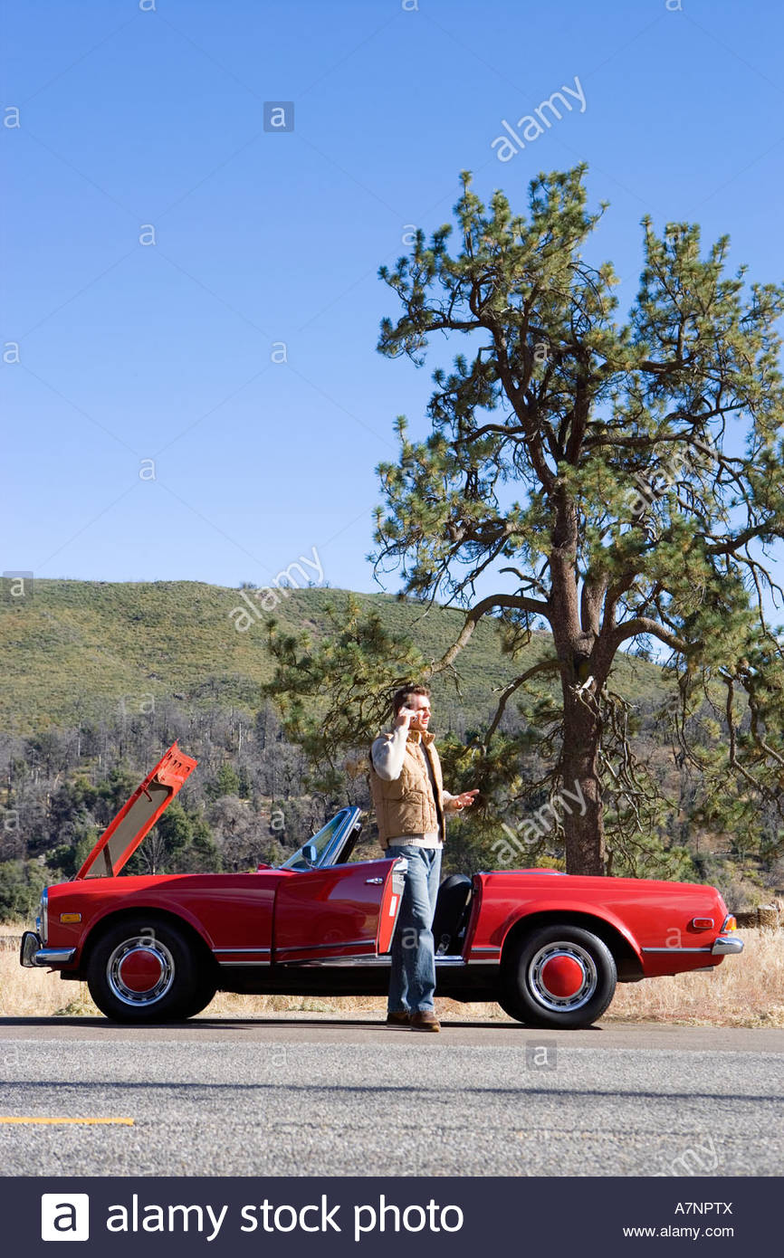 Man standing beside red convertible car on country road experiencing car trouble using mobile phone side view - Stock Image