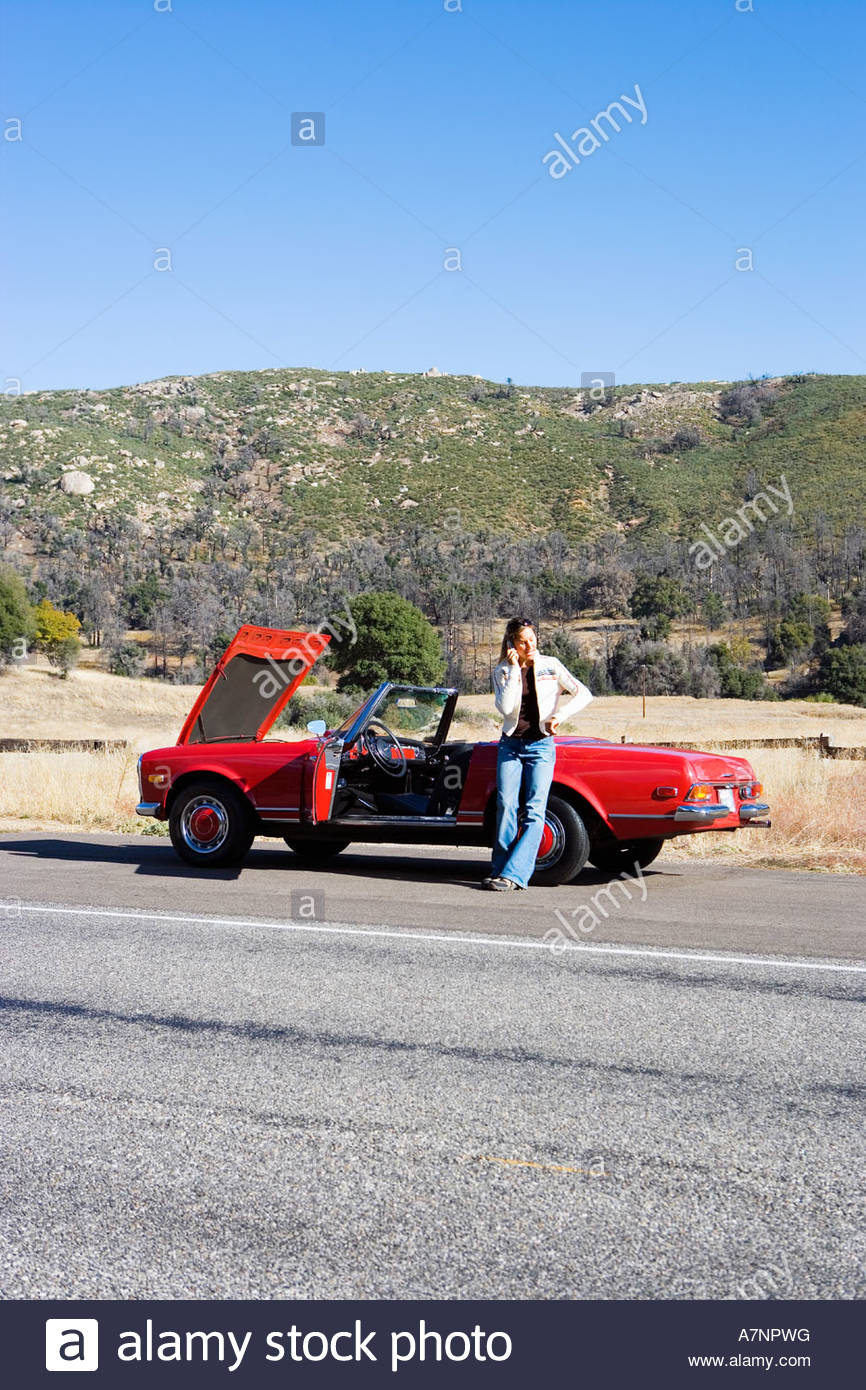 Woman standing beside red convertible car on country road experiencing car trouble using mobile phone side view - Stock Image