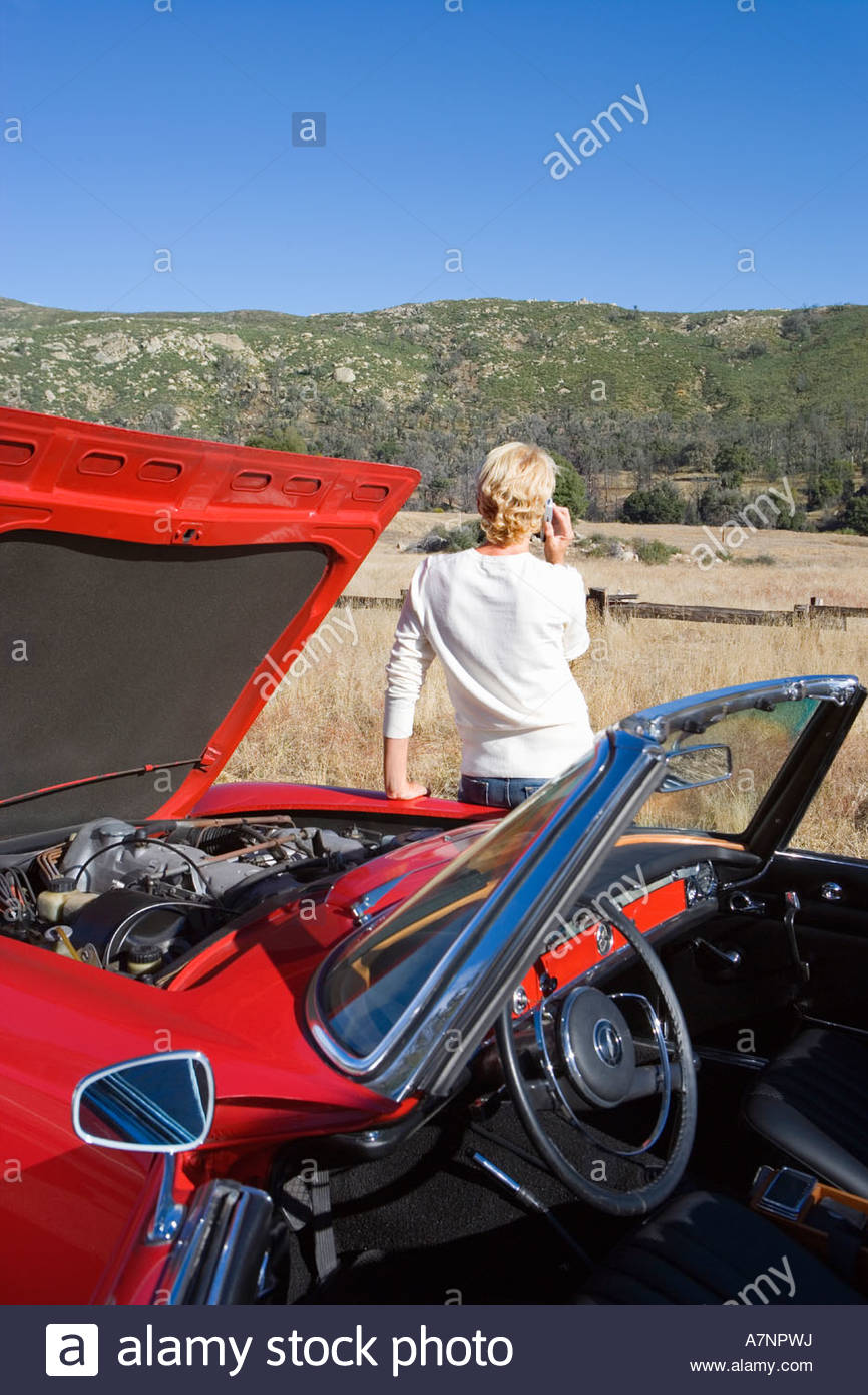Woman standing beside red convertible car on country road experiencing car trouble using mobile phone rear view - Stock Image