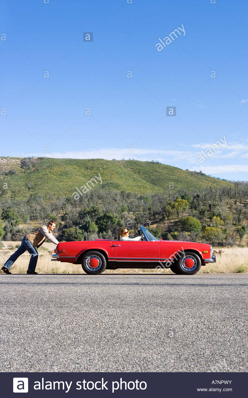 Couple experiencing car trouble on country road man pushing car woman sitting in driver s seat side view - Stock Image