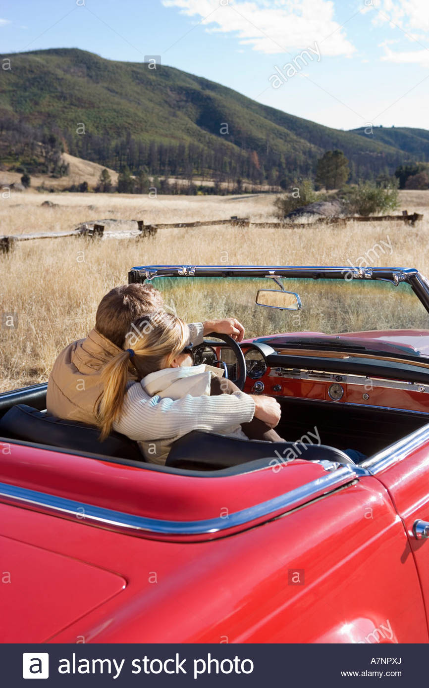 Couple driving in red convertible car on country road man with arm around woman rear view - Stock Image
