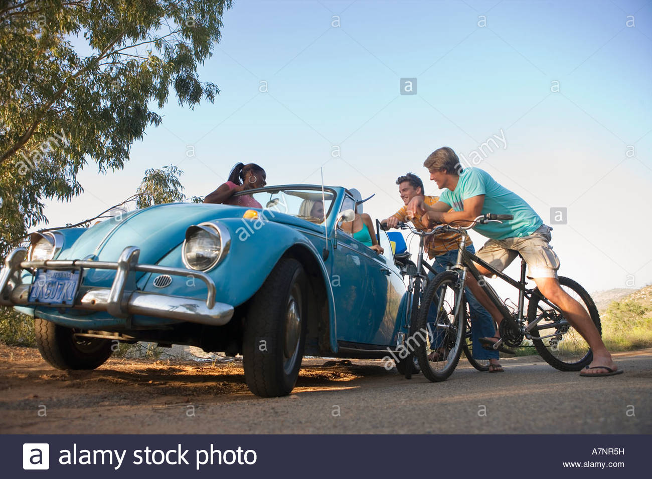 Group of friends talking at roadside teenage boys 17 19 on bicycles teenage girls in blue car Stock Photo