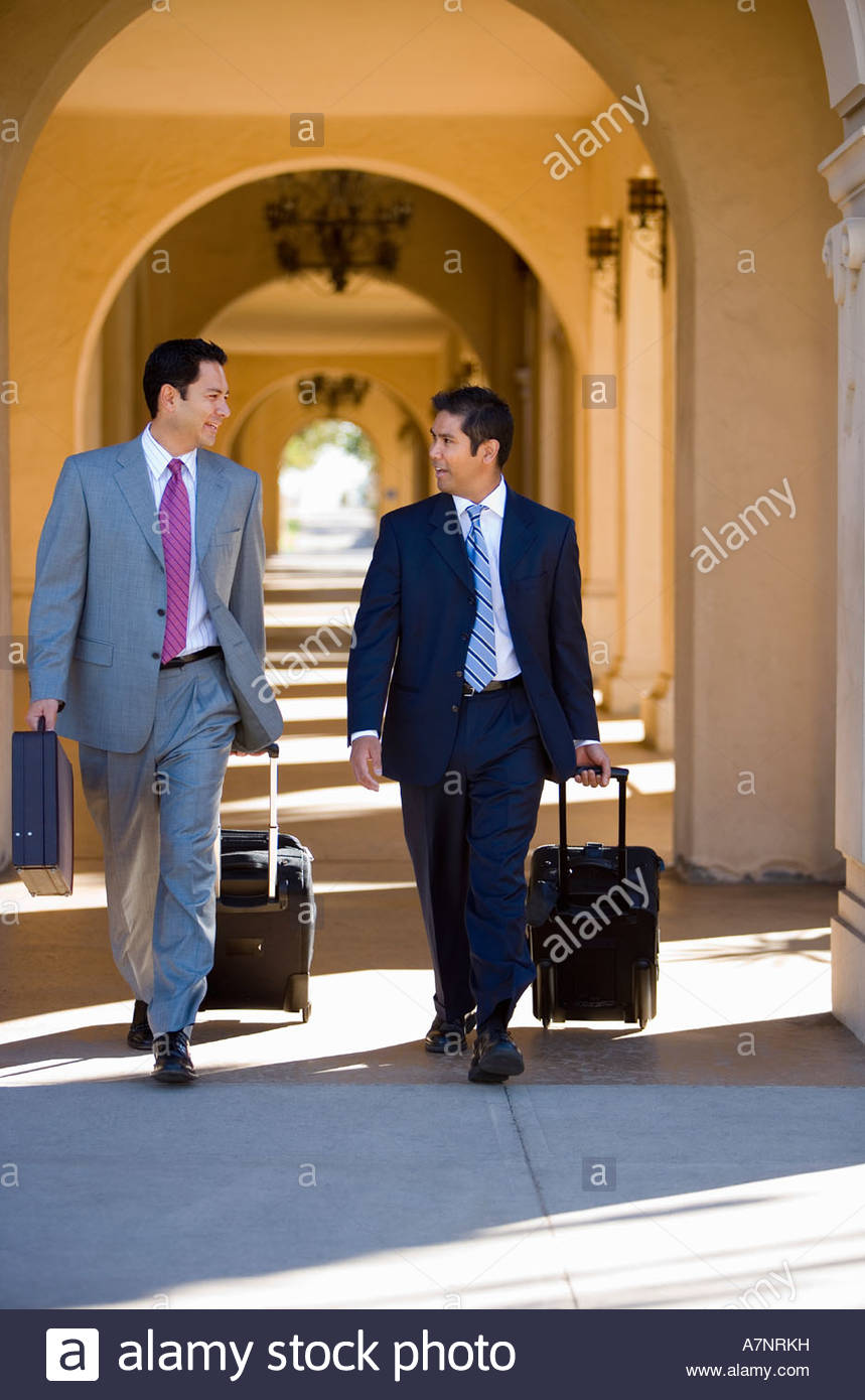 Two businessmen walking side by side in building arcade luggage in tow talking front view - Stock Image