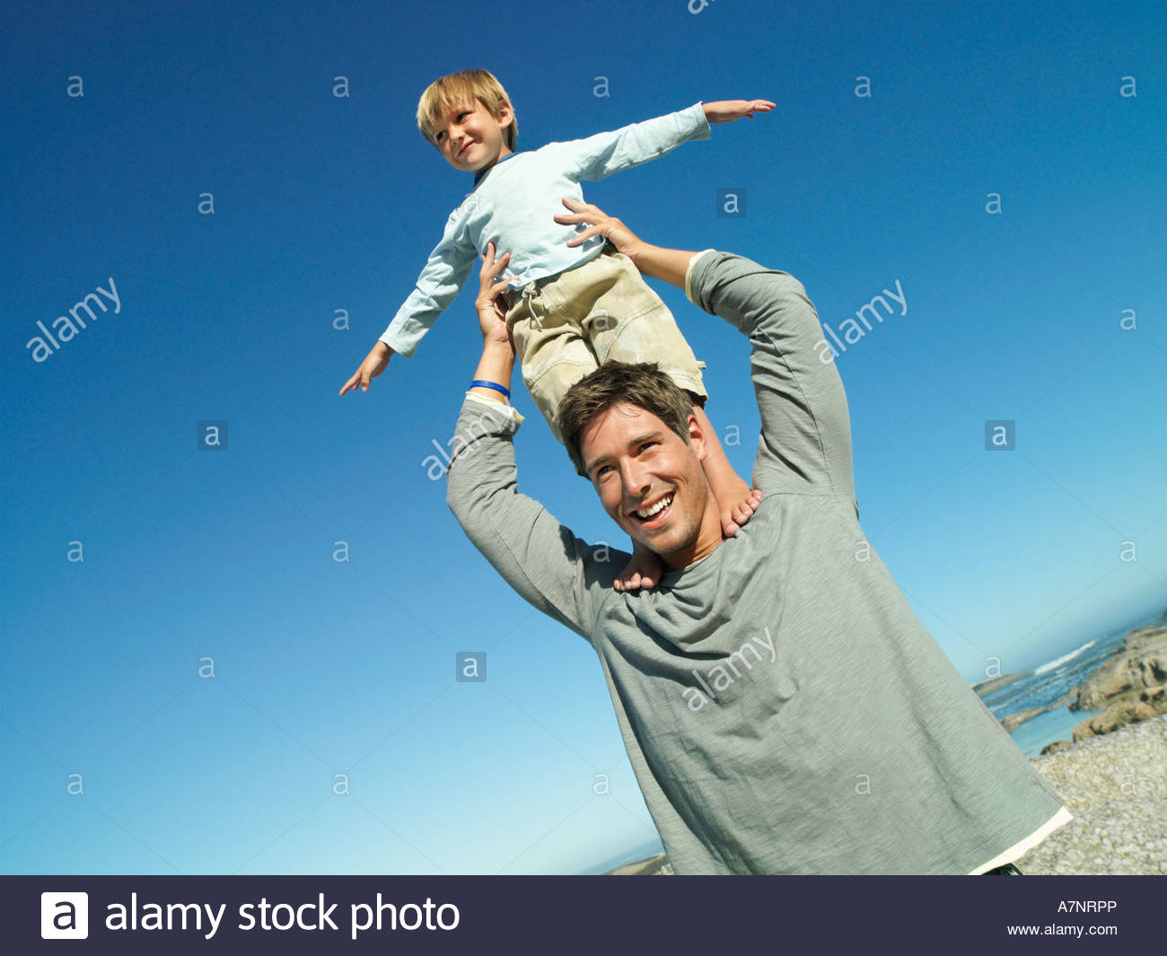 Boy 4 6 standing on father s shoulders at beach arms out smiling tilt - Stock Image