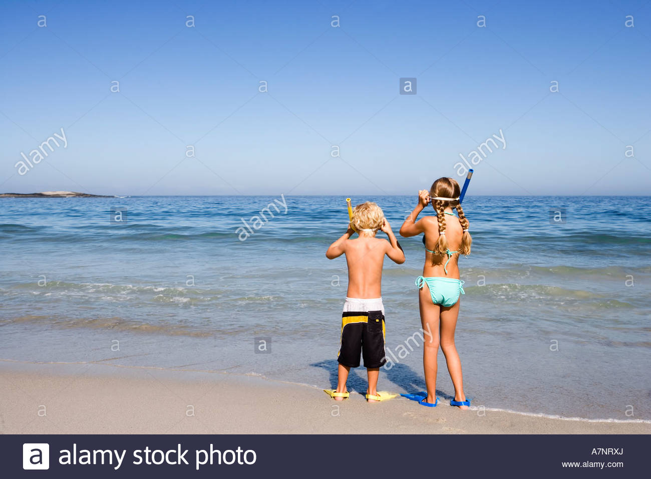 Boy 4 6 and girl 5 7 standing side by side on sandy beach at water s edge wearing snorkels rear view - Stock Image