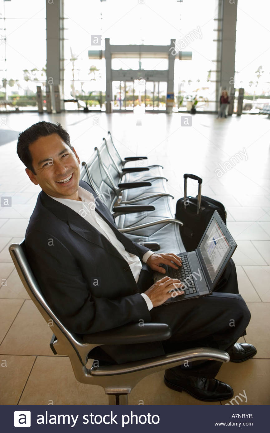 Businessman waiting in airport departure lounge using laptop smiling side view portrait - Stock Image