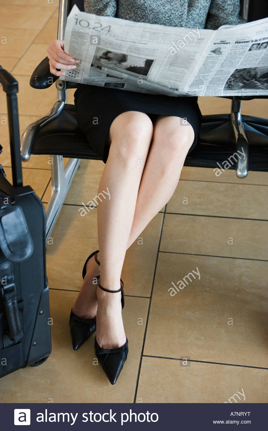 Businesswoman waiting in airport departure lounge reading newspaper low section front view - Stock Image