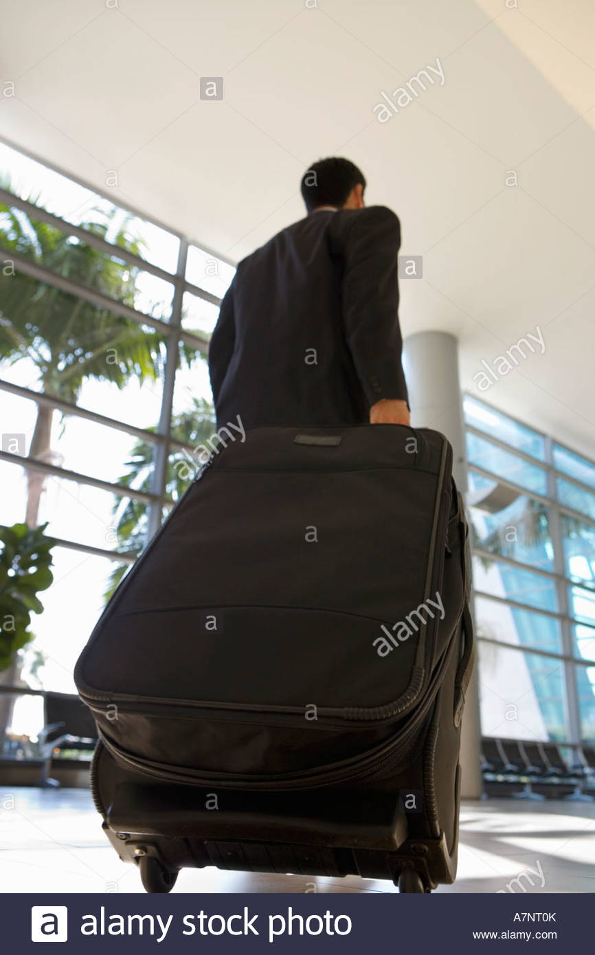 Businessman walking in airport terminal with luggage in tow rear view surface level - Stock Image