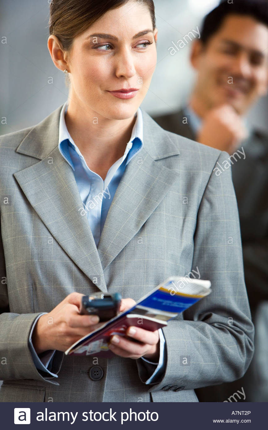 Businesswoman standing in airport terminal holding mobile phone and ticket making sideways glance - Stock Image