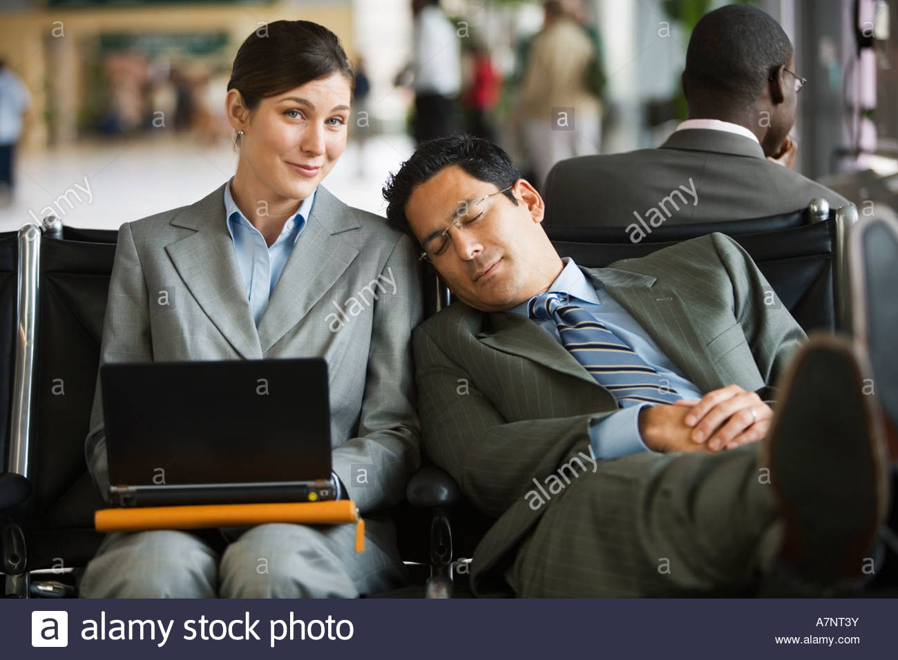 Two business people sitting in airport terminal tired man resting head against woman s shoulder woman using laptop - Stock Image