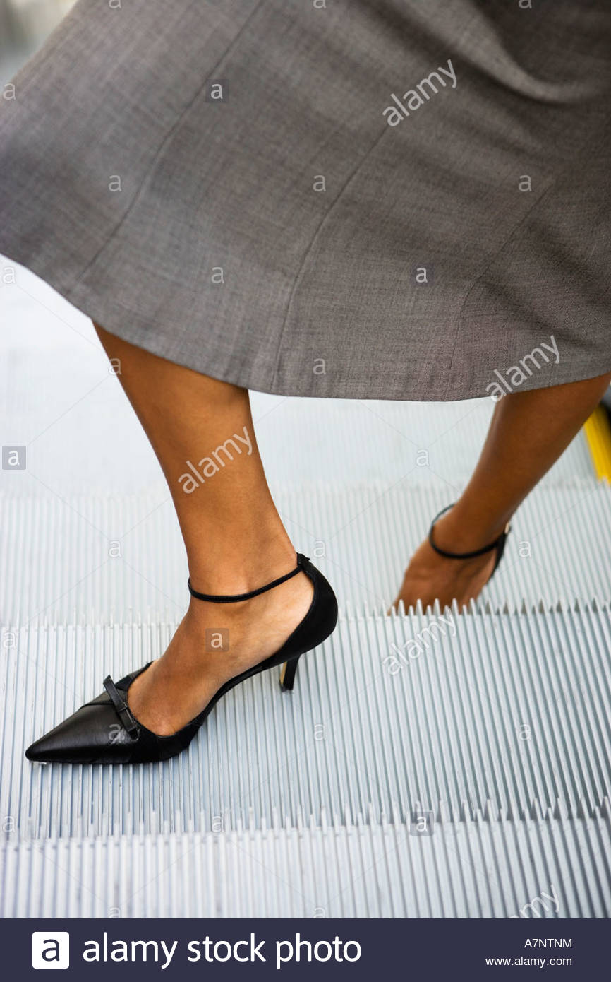 Businesswoman in grey skirt and high heels standing on escalator close up low section - Stock Image