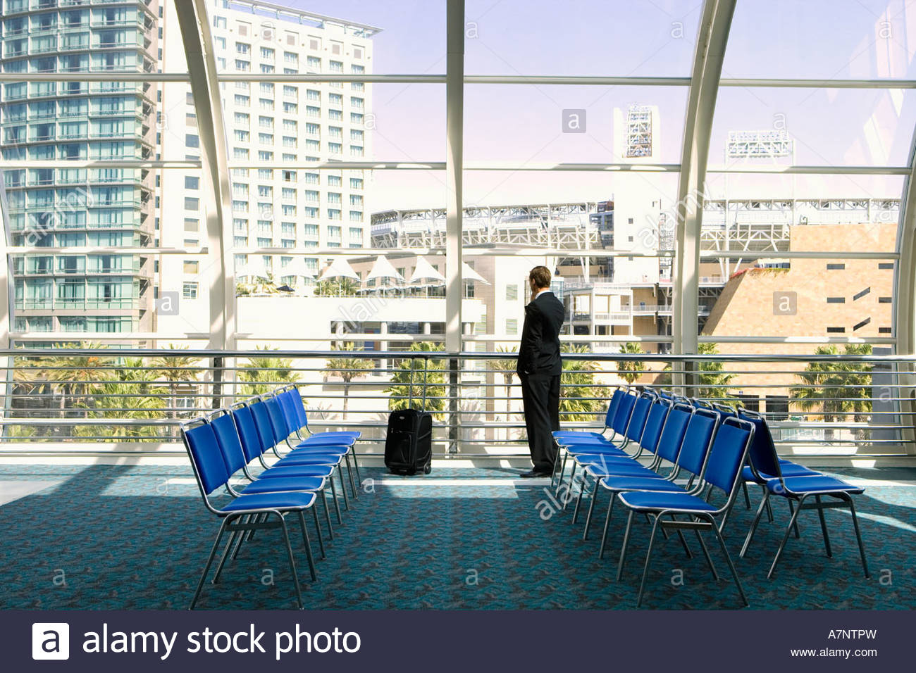 Solitary businessman waiting in airport departure lounge looking through large window at urban scene rear view - Stock Image