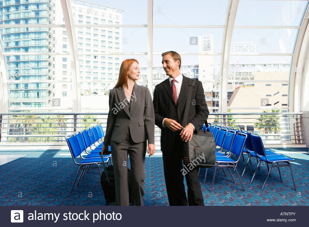Businessman and woman walking with luggage in tow in airport departure lounge smiling front view - Stock Image