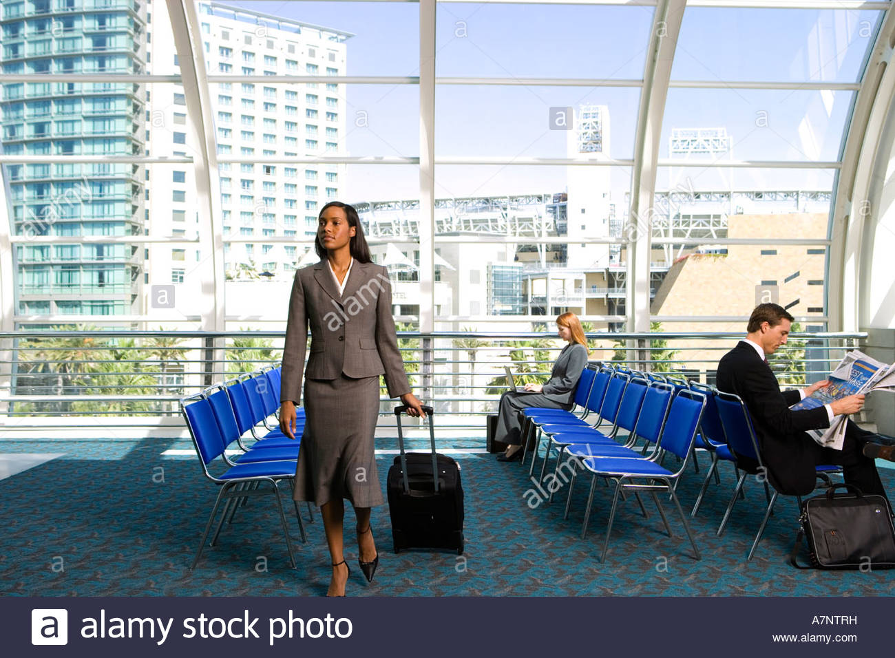 Businesswoman walking in airport departure lounge with luggage in tow businessman reading newspaper - Stock Image