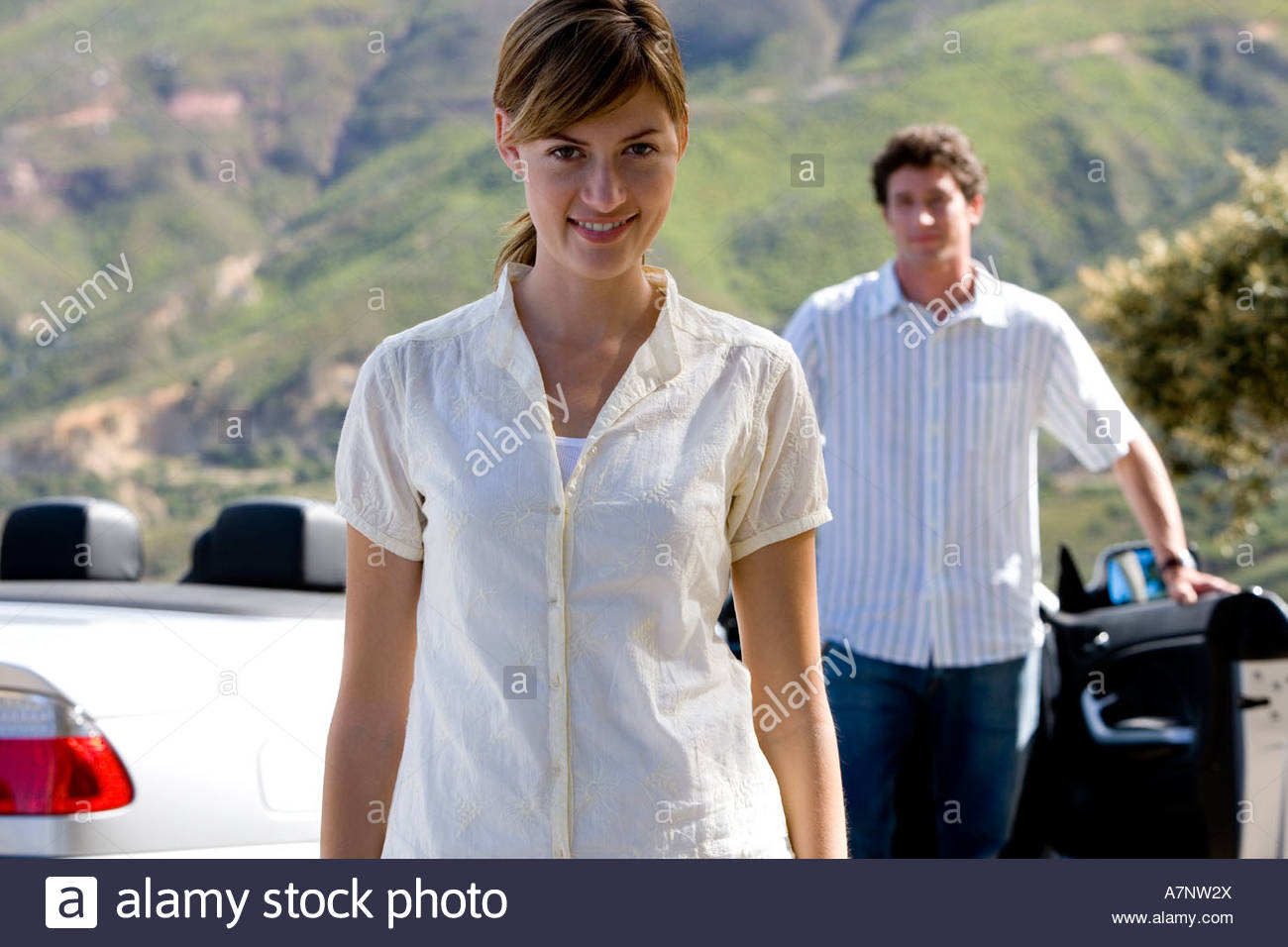 Couple standing beside parked convertible car on mountain roadside focus on woman smiling portrait - Stock Image