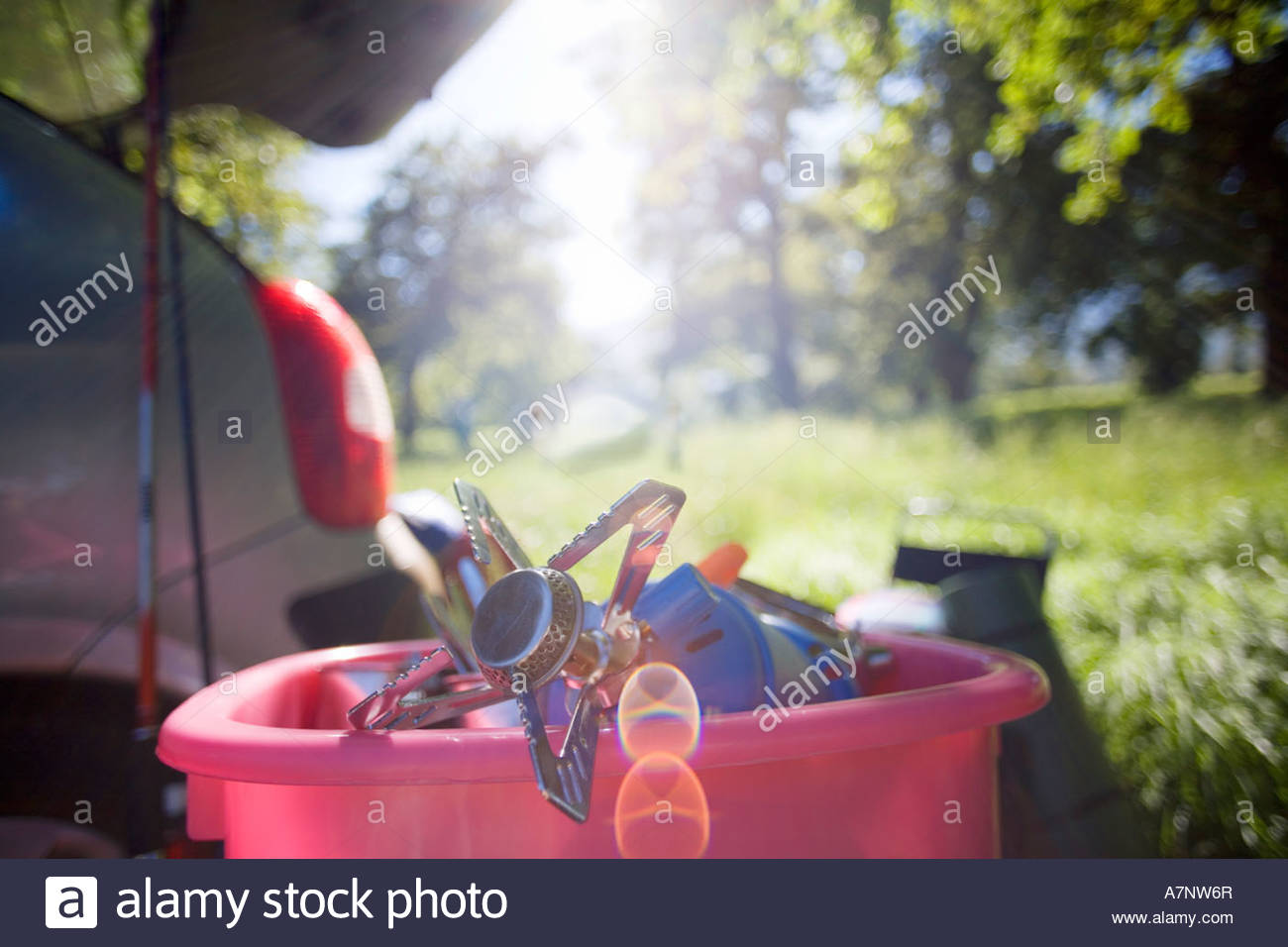 Parked car in woodland clearing focus on camping stove in pink container backlit Stock Photo