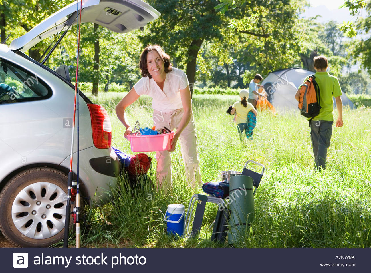 Family unloading car on camping trip focus on woman holding pink container beside car boot smiling portrait Stock Photo