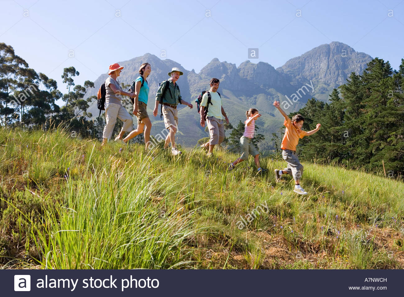 Multi generational family hiking on mountain trail walking in line boy 8 10 leading side view - Stock Image