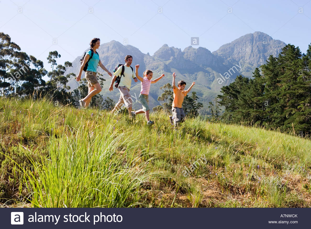 Family hiking on mountain trail walking in line boy 8 10 leading side view - Stock Image