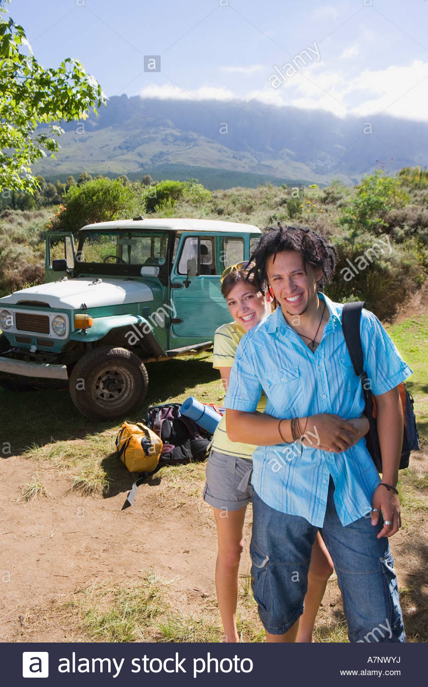 Young couple standing near parked jeep at start of camping holiday woman embracing man smiling portrait - Stock Image