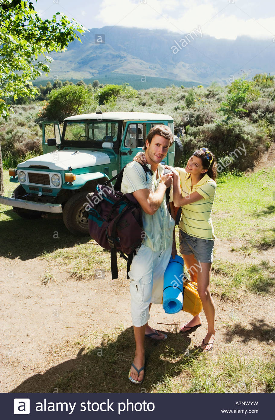 Young couple unloading parked jeep at start of camping holiday woman assisting man smiling portrait - Stock Image