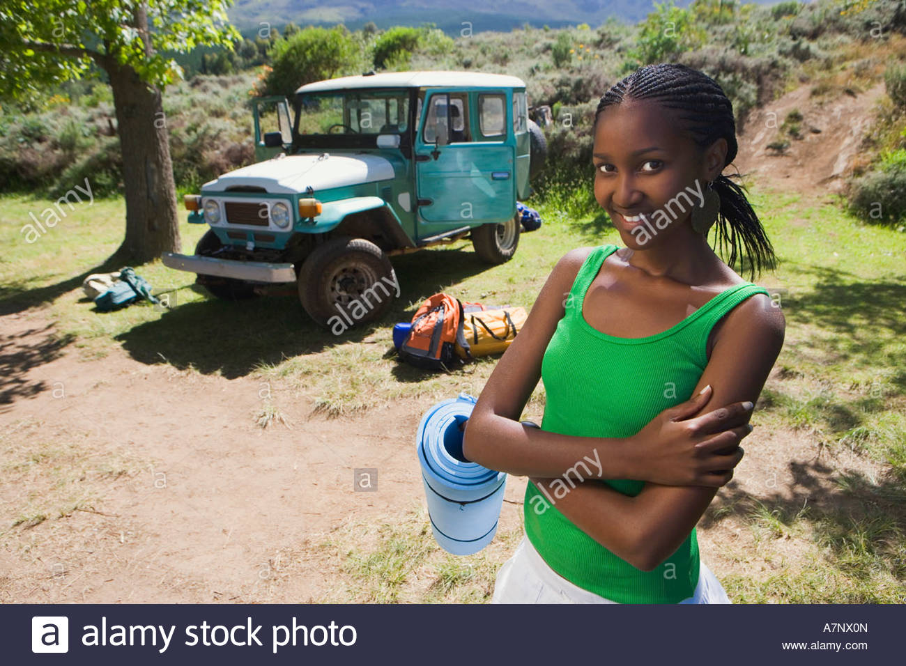 Young woman unloading parked jeep at start of camping holiday holding sleeping mat smiling portrait - Stock Image