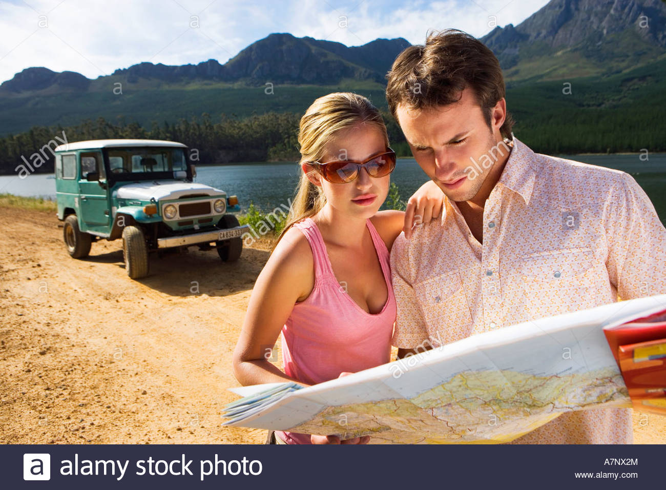 Young couple standing near parked jeep on dirt track beside lake consulting map - Stock Image