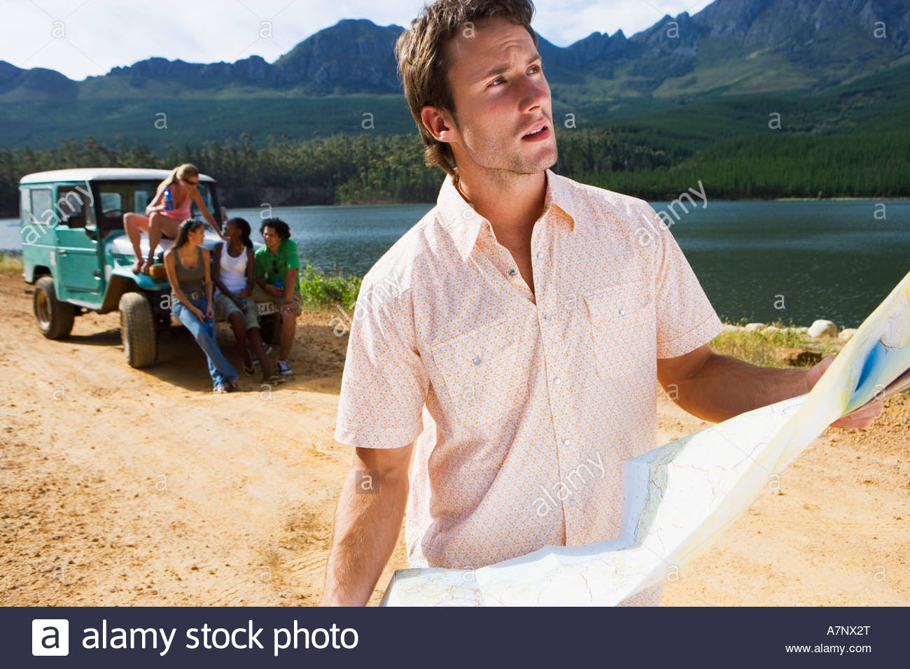 Four young adults waiting by parked jeep on dirt track beside lake focus on man consulting map in foreground - Stock Image