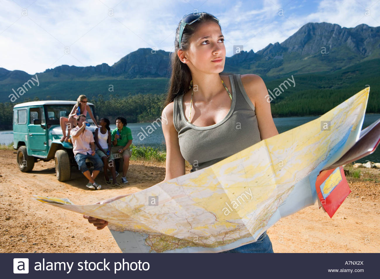 Four young adults waiting near parked jeep on dirt track beside lake focus on woman consulting map in foreground - Stock Image