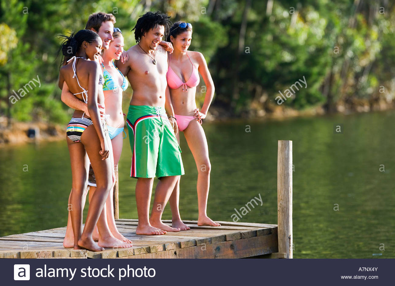Five young adults in swimwear standing side by side on lake jetty smiling side view Stock Photo