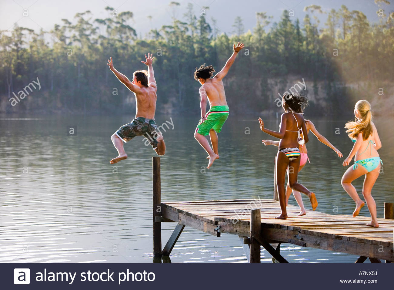 Five young adults in swimwear jumping from jetty into lake rear view - Stock Image