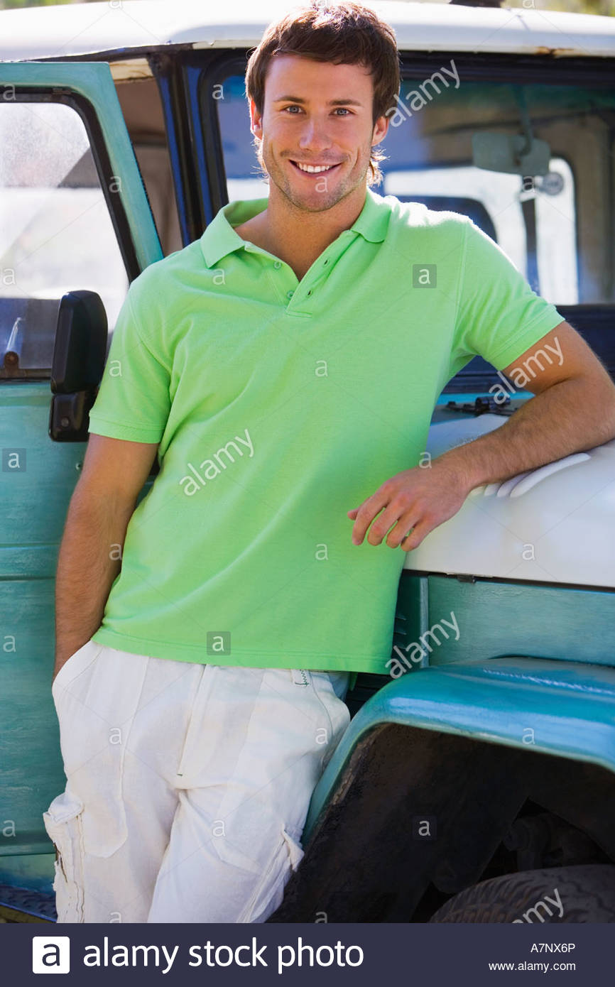 Young man in green polo shirt leaning against parked jeep smiling portrait - Stock Image