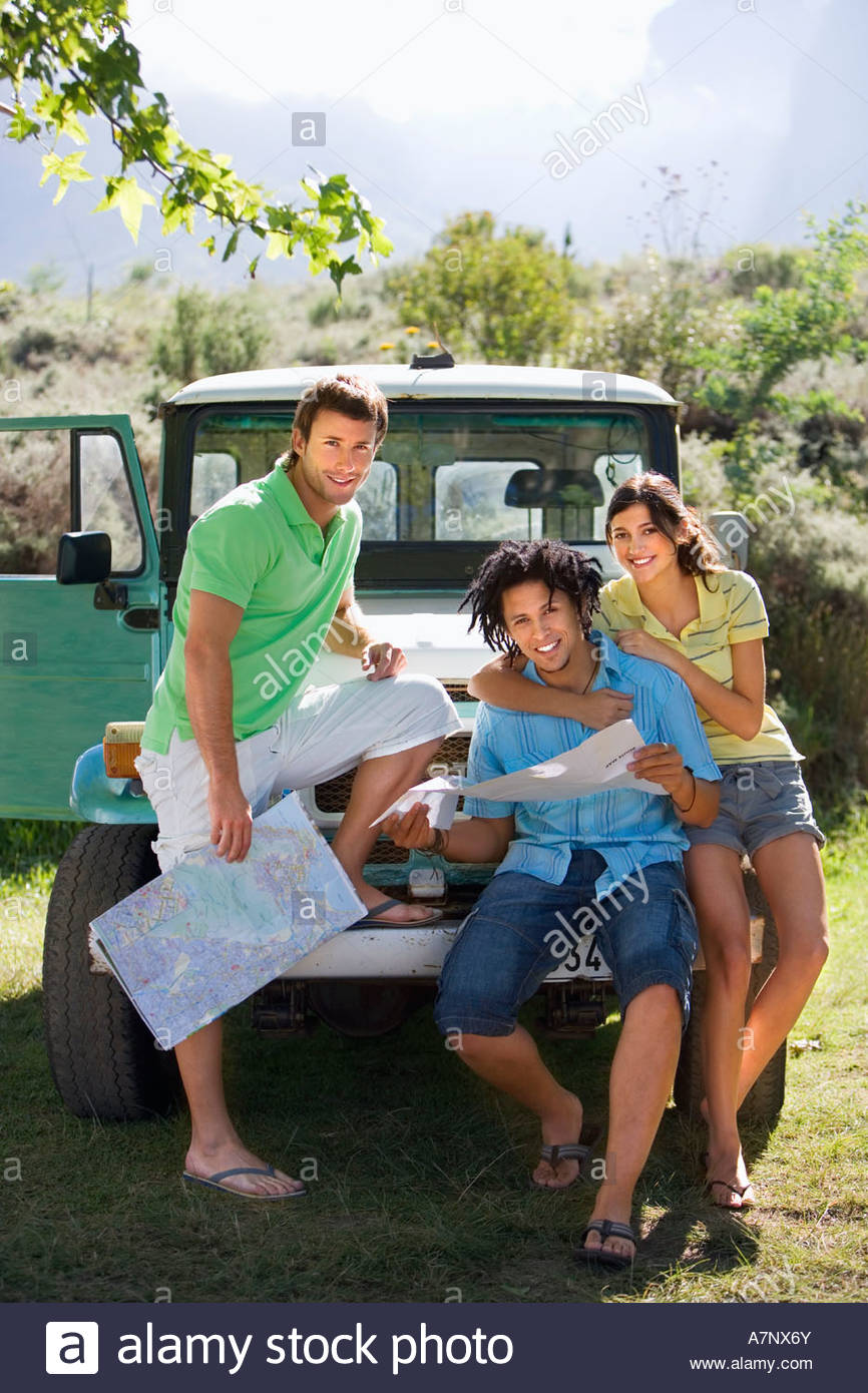 Young woman and two male friends leaning against parked jeep consulting road map smiling portrait - Stock Image