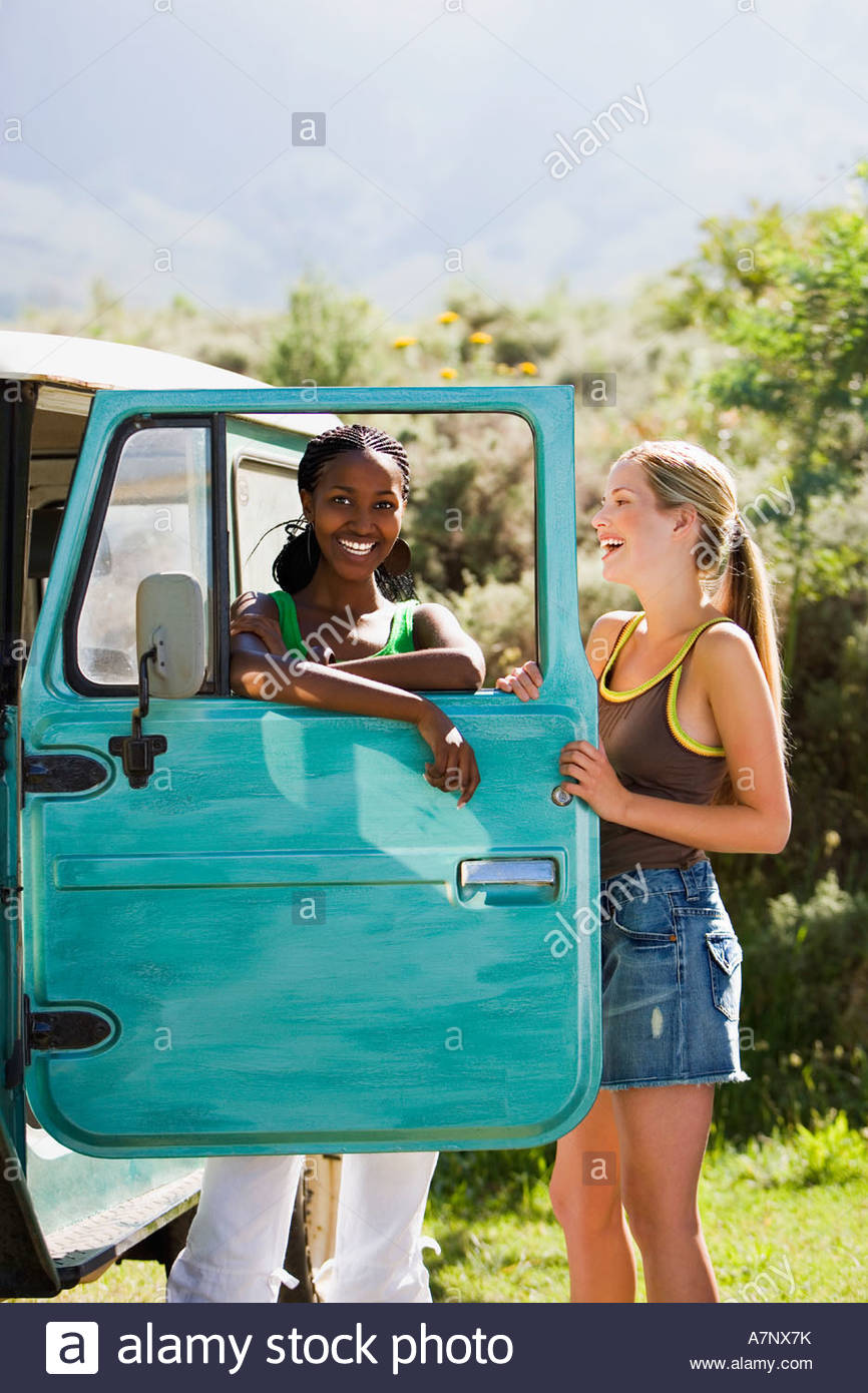 Two young women standing beside parked jeep leaning on turquoise door laughing portrait - Stock Image