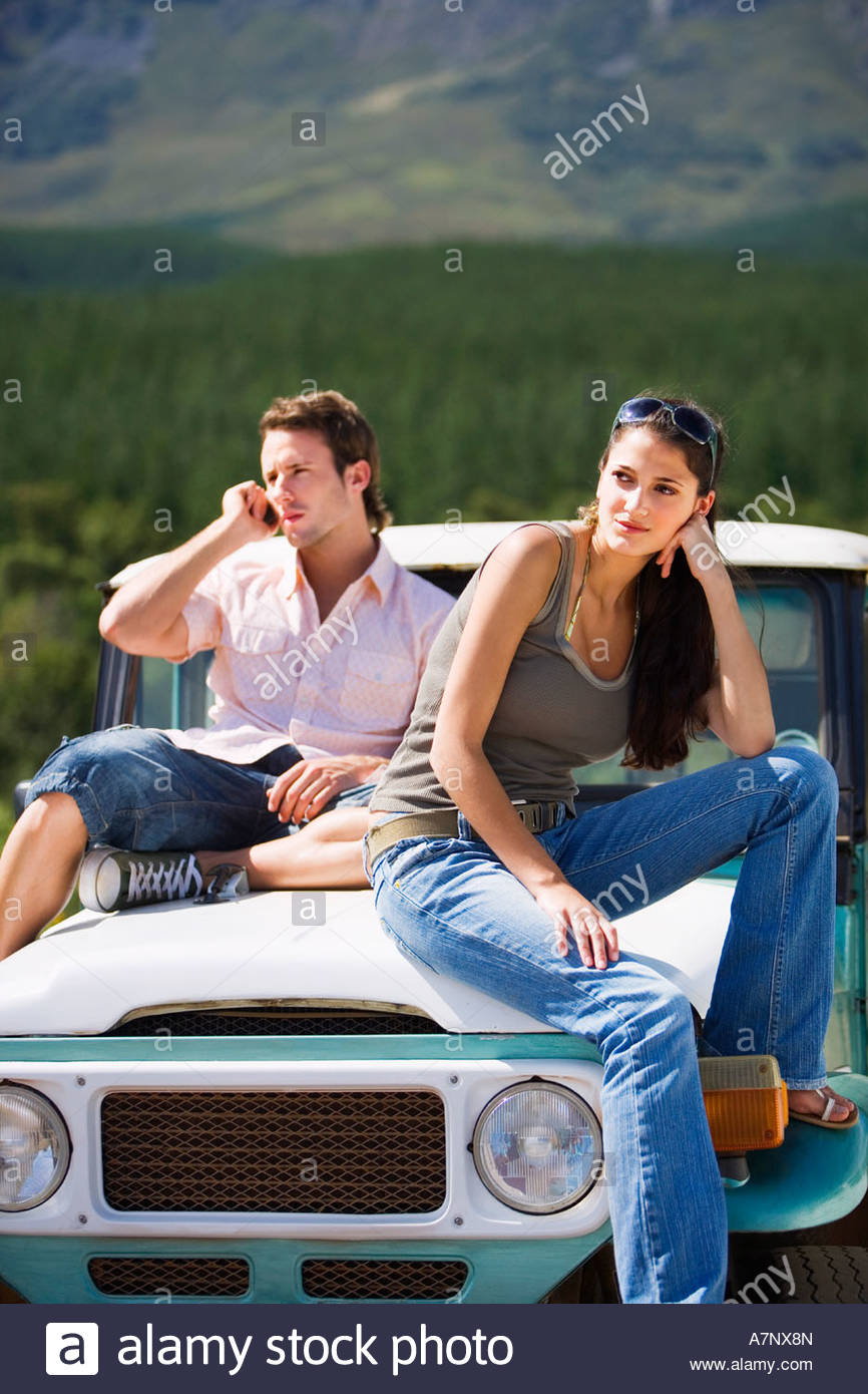 Young couple sitting on bonnet of parked jeep in mountain valley man using mobile phone - Stock Image