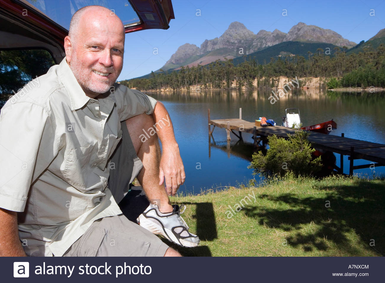 Mature man sitting in boot of parked SUV smiling side view portrait lake and jetty in background - Stock Image