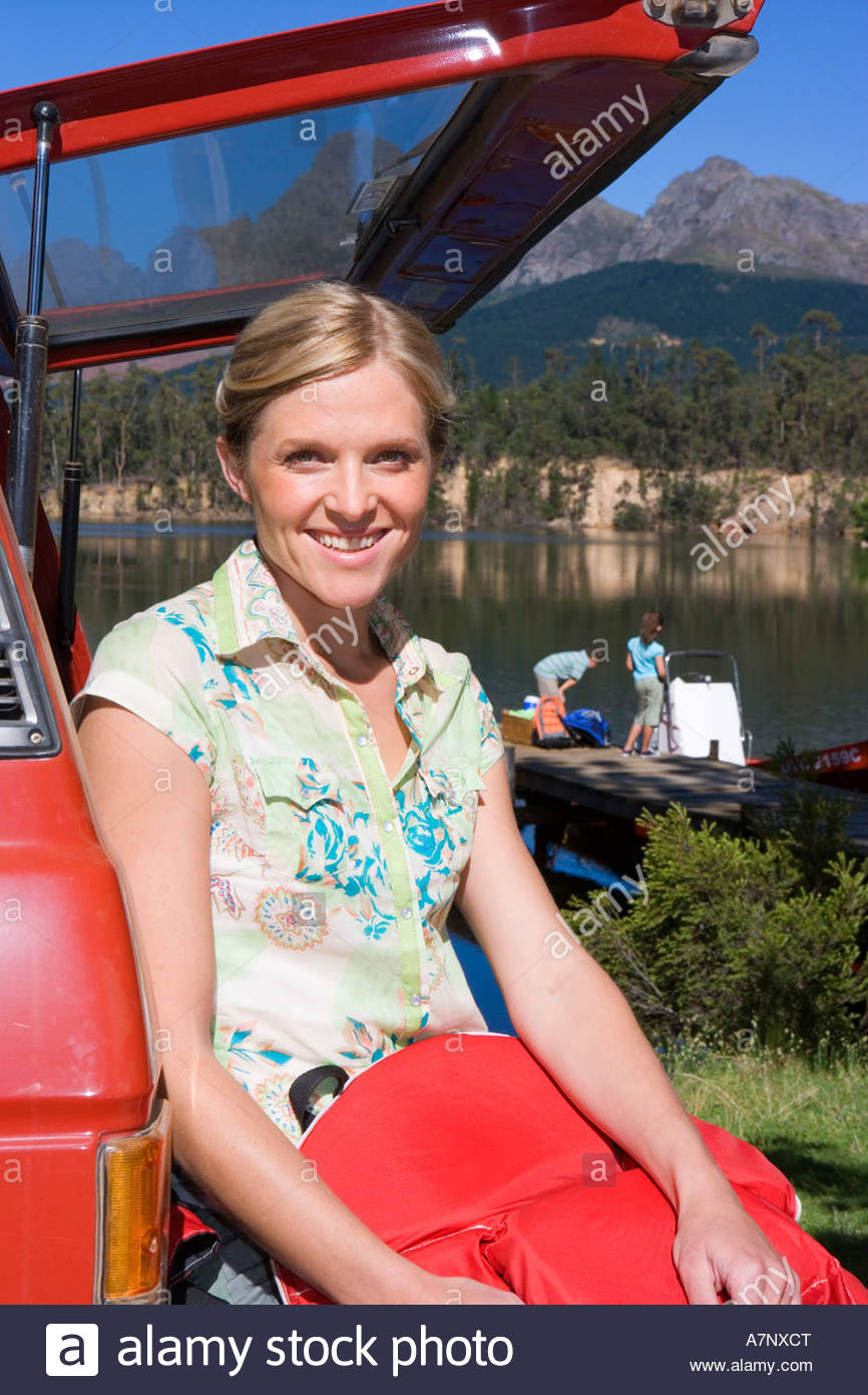 Woman sitting in boot of parked SUV holding red life jacket smiling portrait lake and jetty in background - Stock Image