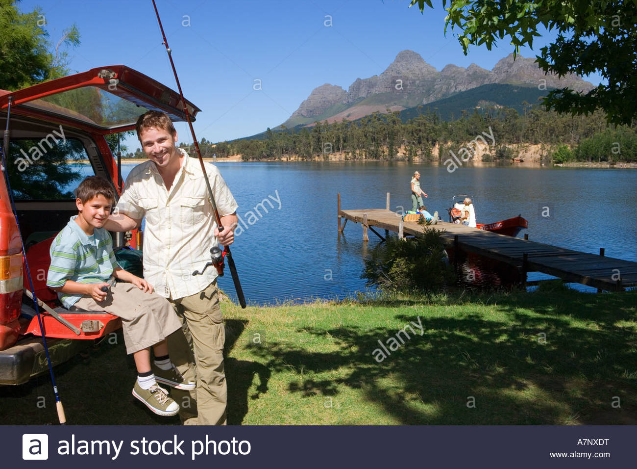 Father and son 8 10 with fishing rod beside SUV smiling portrait rest of family standing on lake jetty near boat Stock Photo