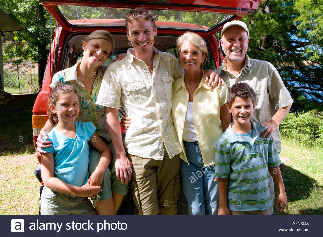 Multi generational family standing beside parked SUV smiling portrait - Stock Image