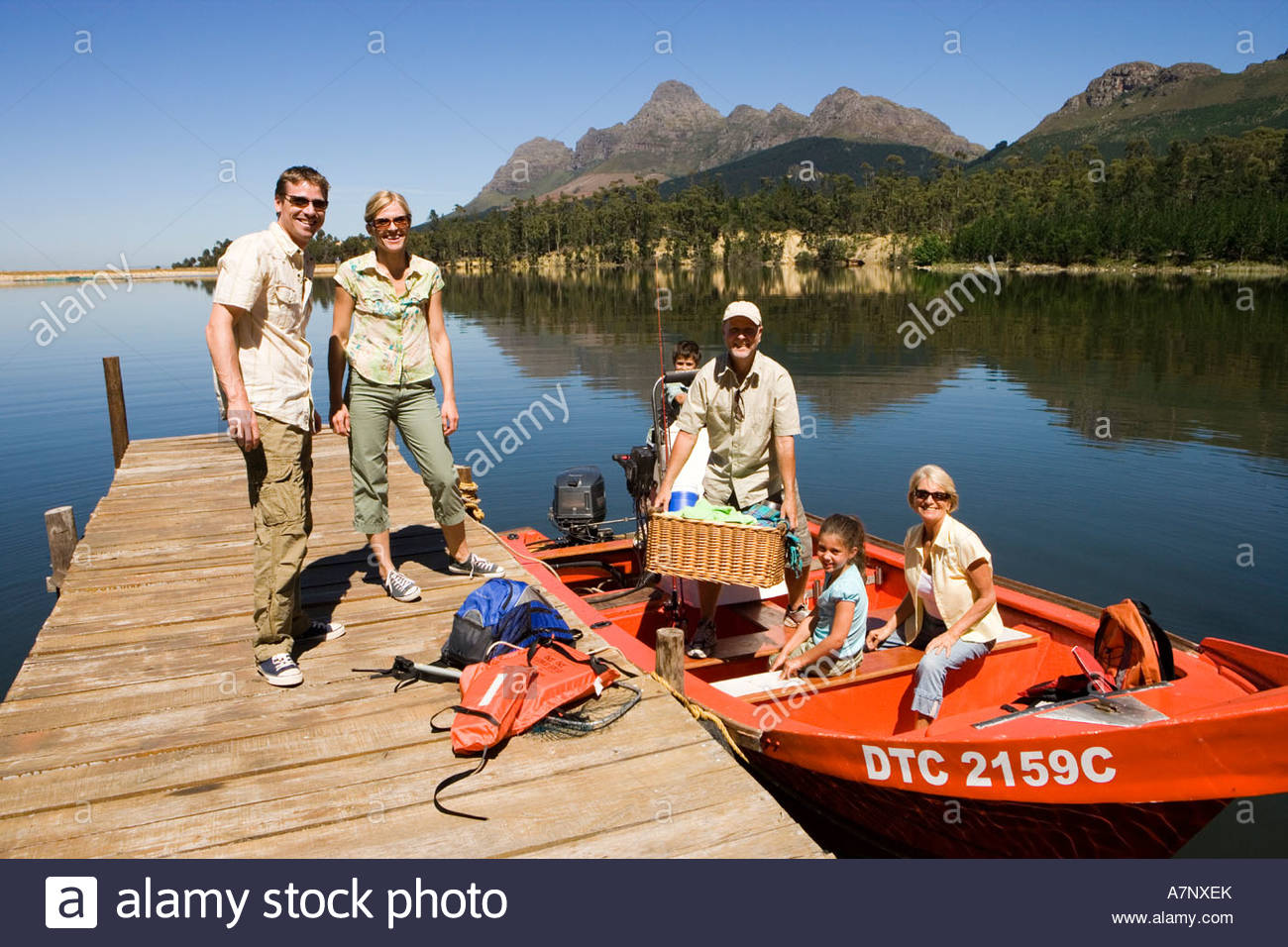 Multi generational family loading motorboat with provisions on lake jetty smiling portrait Stock Photo