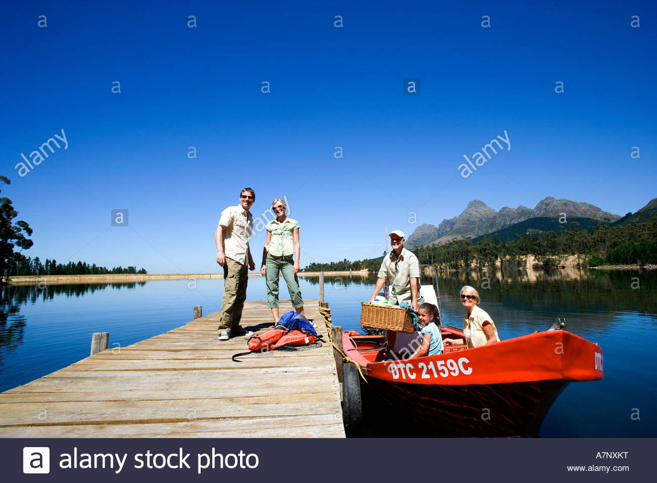 Multi generational family loading motorboat with provisions at lake jetty grandfather holding picnic hamper - Stock Image