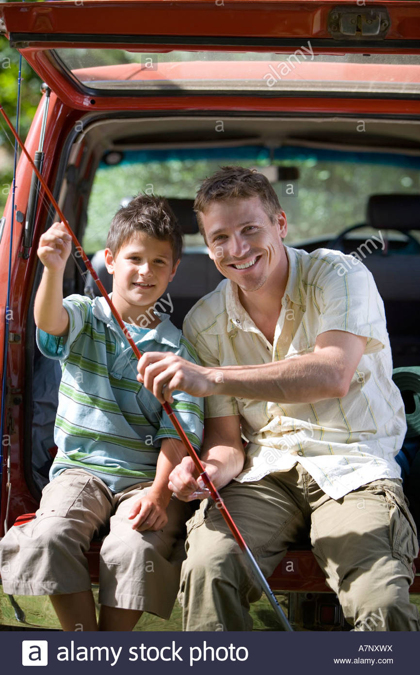 Father and son 8 10 sitting in boot of parked SUV holding fishing rods smiling portrait - Stock Image